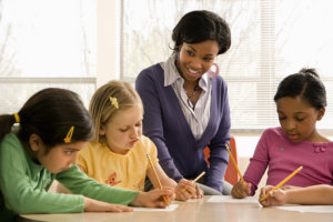teacher guiding her students in writing